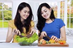 Азиатские женщины подготавливая салат в кухне Стоковые Фотографии RF