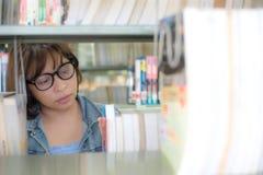 Азиатские женщины студента находя книга для читать в библиотеке стоковое фото rf