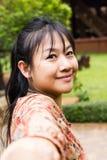 Азиатские женщины усмехаясь, дама длинных волос стороны конца-вверх азиатская в коричневом цвете Стоковая Фотография RF