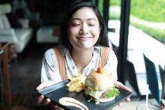 Азиатские женщины усмехаясь и счастливые и наслаженные съесть гамбургеры на c стоковое изображение rf