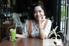 Азиатские женщины читая и усмехаясь и счастливый ослаблять в кофе s стоковые фото