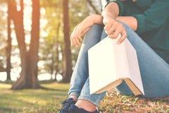 Азиатские женщины читая книгу в природе Стоковые Изображения