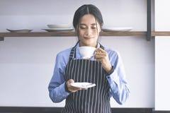 Азиатские женщины barista пахнуть кофе стоковые изображения