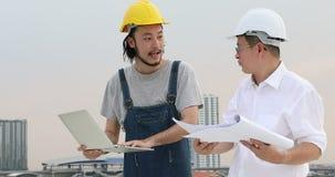 Азиатские инженеры стоя, что на крыше, молодой тетради пользы инженера обсудить о whit светокопии старую видеоматериал