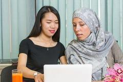 Азиатские и мусульманские девушки работая на компьтер-книжке Стоковая Фотография