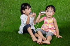 Азиатские китайские дети играя с телефоном жестяной коробки Стоковая Фотография RF