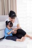 Азиатские китайские мать и дочь используя smartphone на поле Стоковая Фотография