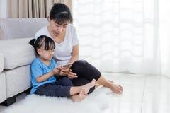 Азиатские китайские мать и дочь используя smartphone на поле Стоковое Фото