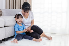 Азиатские китайские мать и дочь используя smartphone на поле Стоковые Фото