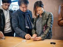 Азиатские клиенты пар этничности на Яблоке хранят iPhone x Стоковые Изображения