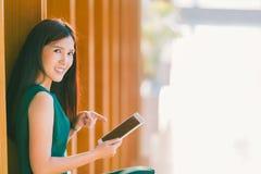 Азиатские коммерсантка или студент колледжа используя и указывающ на цифровую таблетку во время захода солнца, на современные офи Стоковое фото RF