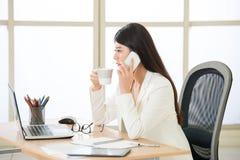 Азиатские коммерсантки используя умный телефон и смотрящ Sc компьютера Стоковые Фотографии RF