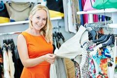 азиатские красивейшие кавказские одежды одевая женскую счастливую внутри помещения смотря женщину магазина модельной покупкы поку Стоковое Изображение RF