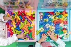 Азиатские маленькие китайские девушки играя головоломку Стоковые Фото