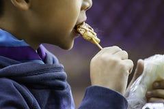 Азиатские мальчики едят липкий рис и жаркое свинины, еда просто и популярно для еды завтрака в Таиланде стоковые фотографии rf