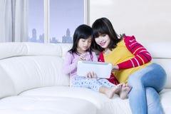 Азиатские мать и ребенок используют таблетку в квартире Стоковые Изображения
