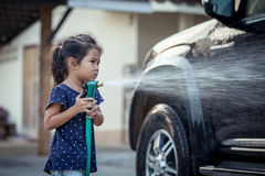 азиатские маленькие девочки помогая родителю моя автомобиль Стоковые Изображения