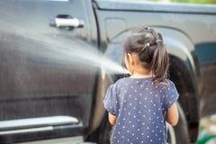 азиатские маленькие девочки помогая родителю моя автомобиль Стоковая Фотография