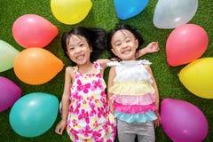 Азиатские маленькие китайские девушки лежа на траве среди красочного ballo Стоковые Фотографии RF