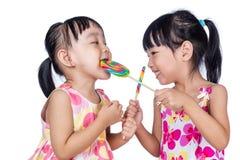 Азиатские маленькие китайские девушки есть леденец на палочке Стоковая Фотография