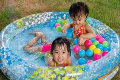 Азиатские маленькие китайские девушки играя в раздувном резиновом Swimm Стоковые Фото