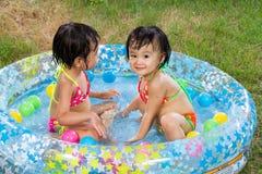 Азиатские маленькие китайские девушки играя в раздувном резиновом Swimm Стоковое фото RF