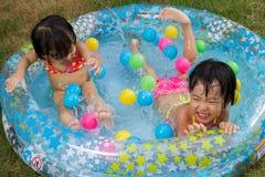 Азиатские маленькие китайские девушки играя в раздувном резиновом Swimm Стоковые Фотографии RF