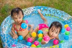 Азиатские маленькие китайские девушки играя в раздувном резиновом Swimm Стоковая Фотография