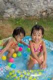 Азиатские маленькие китайские девушки играя в раздувном резиновом Swimm Стоковые Изображения