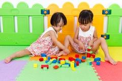 Азиатские маленькие китайские девушки играя деревянные блоки Стоковое Изображение