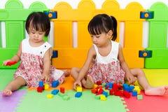 Азиатские маленькие китайские девушки играя деревянные блоки Стоковая Фотография