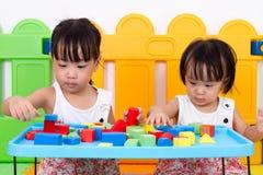 Азиатские маленькие китайские девушки играя деревянные блоки Стоковое фото RF
