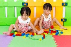 Азиатские маленькие китайские девушки играя деревянные блоки Стоковые Изображения