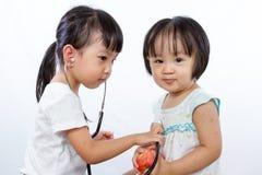 Азиатские маленькие китайские девушки играя как доктор и пациент с St Стоковое Изображение