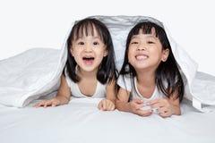 Азиатские маленькие китайские девушки играя на кровати Стоковое фото RF