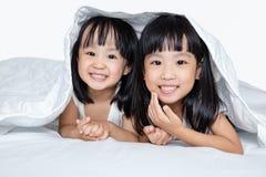 Азиатские маленькие китайские девушки играя на кровати Стоковое Изображение