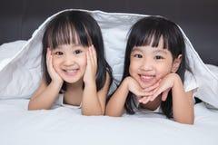 Азиатские маленькие китайские девушки играя на кровати Стоковое Изображение RF