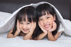 Азиатские маленькие китайские девушки играя на кровати Стоковая Фотография