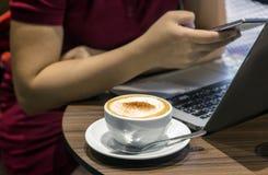 Азиатские мобильный телефон и тетрадь пользы девушки на таблице кафа Стоковая Фотография RF