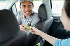 Азиатские молодые водители добросердечно одобряют оплату кредиткой стоковое фото rf