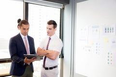 Азиатские молодые люди бизнесмена 2 держа доску сзажимом для бумаги и обсуждая работу в конференц-зале Стоковые Фото