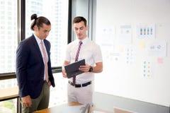 Азиатские молодые люди бизнесмена 2 держа доску сзажимом для бумаги и обсуждая Стоковые Фото