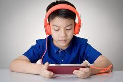 Азиатские наушники изделий мальчика и играть сотовый телефон Стоковые Фото