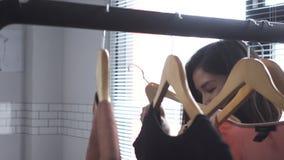 Азиатские одежды покупок женщины Покупатель смотря одежду на рельсе внутри помещения в магазине одежды сток-видео