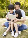 Азиатские отец и дети используя таблетку outdoors Стоковое Изображение RF