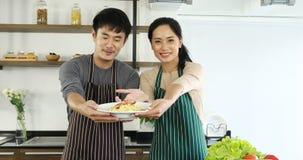 Азиатские пары держали плиту макаронных изделий к камере сток-видео