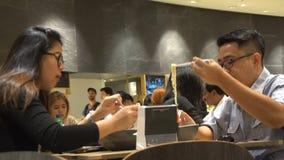 Азиатские пары есть на фуд-корт, Бангкоке, Таиланде - 20-ое апреля 2017 видеоматериал