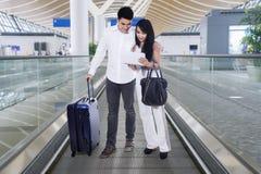 Азиатские пары используя таблетку на эскалаторе авиапорта Стоковая Фотография RF
