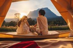 Азиатские пары наслаждаясь на открытом воздухе располагаться лагерем наблюдающ заход солнца в природе стоковые изображения