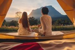 Азиатские пары наслаждаясь на открытом воздухе располагаться лагерем наблюдающ заход солнца в природе стоковое фото